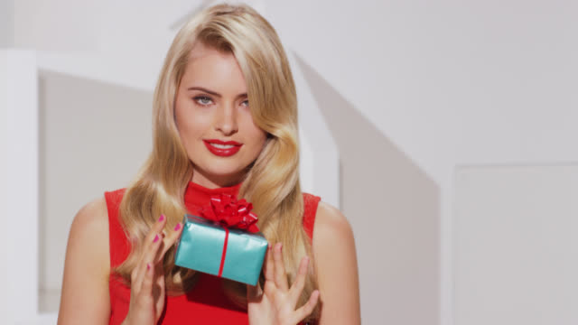 Girl with blonde wavy hair and bold red lipstic shows wrapped gift box to camera