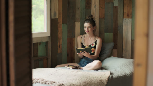 WS SLO MO. Girl with book smiles at camera in rustic treehouse bedroom.