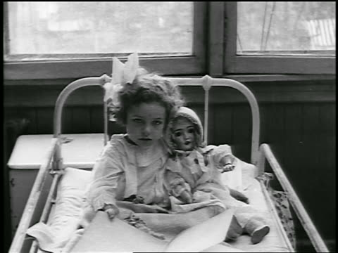 vidéos et rushes de b/w 1920 girl with bow in hair sitting in hospital bed with large doll / detroit, michigan / newsreel - seulement des petites filles