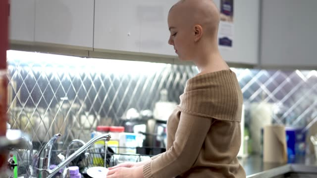 girl with cancer doing dishes - chronic illness stock videos and b-roll footage
