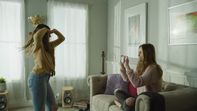 vídeos de stock e filmes b-roll de girl with cell phone recording sister dancing in livingroom / cedar hills, utah, united states - casa