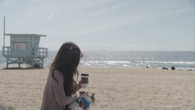Girl with coffee and dog at beach
