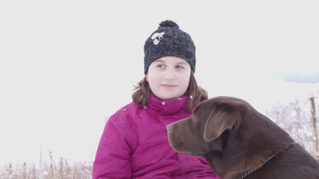 4K Girl with dog getting hit with snowball, slow motion
