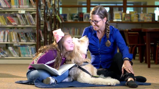 Meisje met Down syndroom en therapie hond in bibliotheek