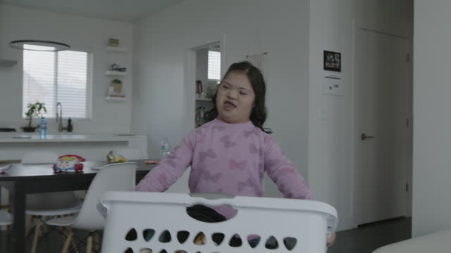 girl with down syndrome carrying clothing in laundry basket / lehi, utah, united states - chores stock videos & royalty-free footage