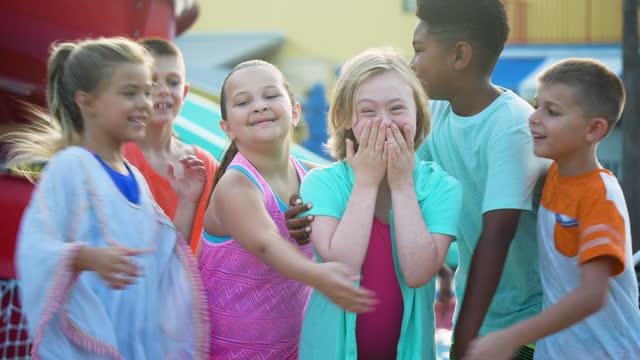 vídeos de stock, filmes e b-roll de garota com síndrome de down, amigos no parque aquático abraçando - miscigenado