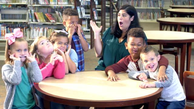 vídeos de stock e filmes b-roll de girl with down syndrome, friends, teacher in library - travessura