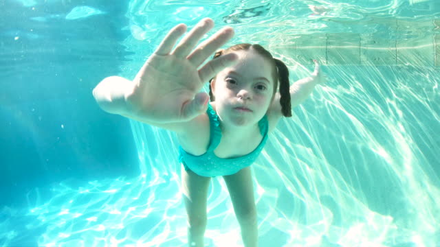 girl with down syndrome playing in swimming pool - surfacing stock videos & royalty-free footage