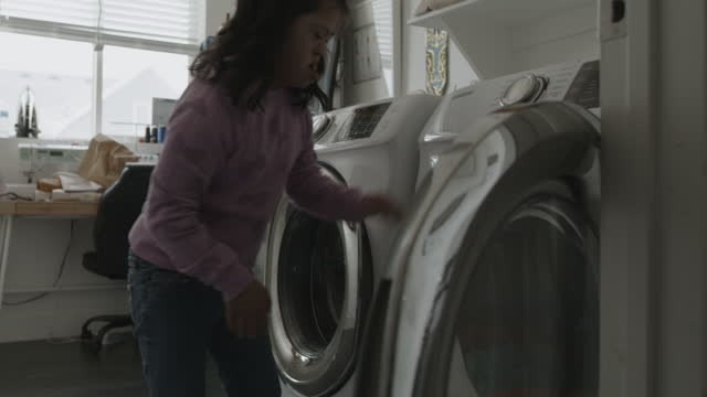girl with down syndrome removing clothing from washing machine / lehi, utah, united states - lehi stock videos & royalty-free footage