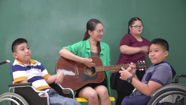 girl with down syndrome standing, dancing, feeling positive emotion, happiness in music class, and therapy with an asian teacher and friends on a wheelchair clapping in the school. beautiful woman playing guitar, sharing relaxation moments with students. - music therapy stock videos & royalty-free footage
