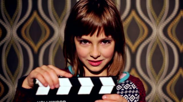 Girl with film slate. Grimace lion.