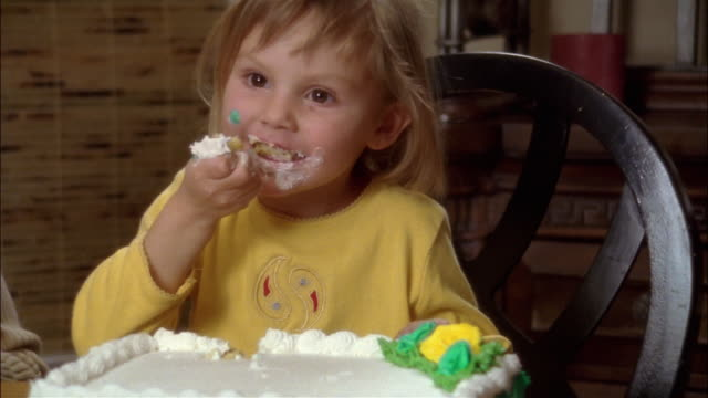 girl with frosting on face using hands to eat birthday cake - icing stock videos and b-roll footage