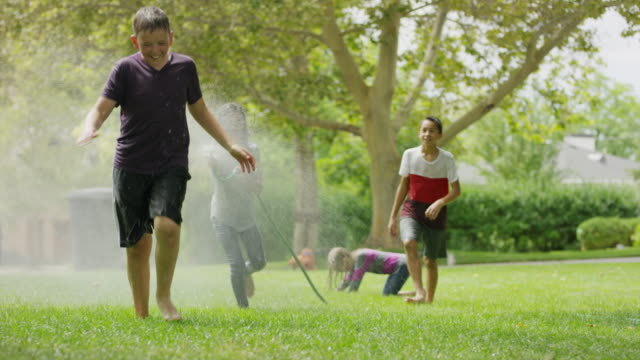 Girl with garden hose spraying friends running in grass / Provo, Utah, United States