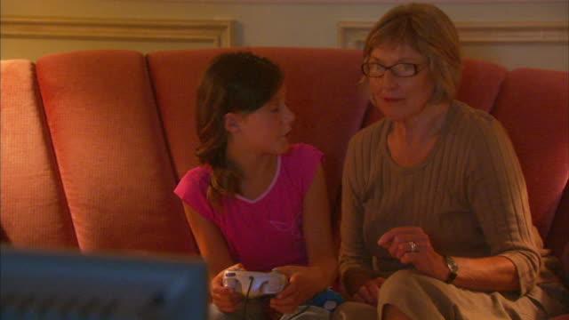 ms girl (8-9) with grandmother playing video game, halifax, nova scotia, canada - dreiviertelansicht stock-videos und b-roll-filmmaterial