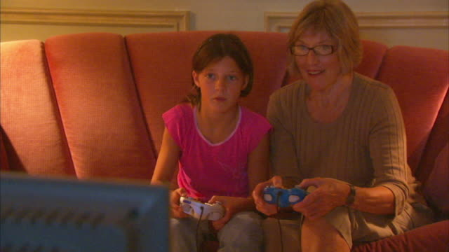 vidéos et rushes de ms girl (8-9) with grandmother playing video game, halifax, nova scotia, canada - cadrage aux genoux