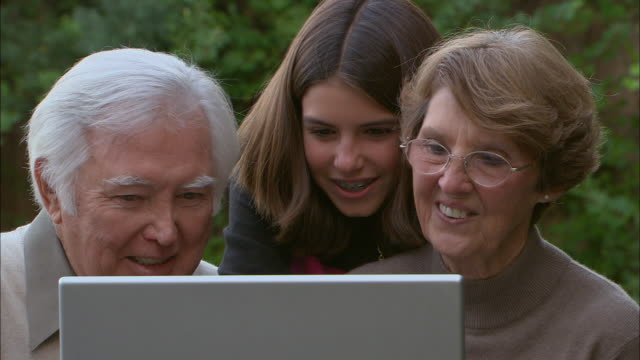 cu, zi, pan, girl (10-11) with grandparents using laptop outdoors, laughing, los angeles, california, usa - brace stock videos and b-roll footage