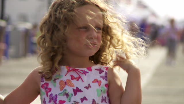 A girl with her curly hair blowing in the wind wipes her mouth.