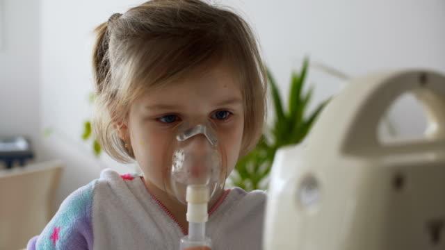 stockvideo's en b-roll-footage met meisje met inhalator in woonkamer - allergie