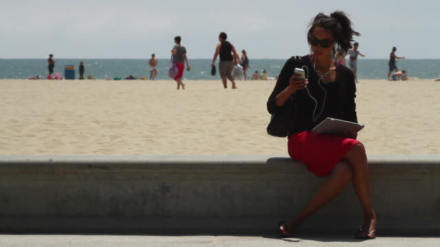 MS Girl with iPhone and iPad at beach / Santa Monica, California, United States