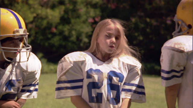 SLO MO MS Girl with long blond hair wearing football jersey / Los Angeles, California, USA