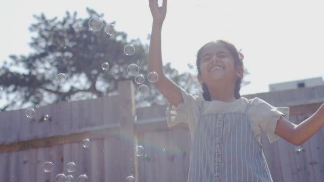 Girl with long braids playing with bubbles in garden