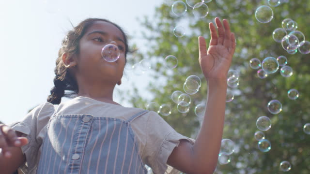 girl with long braids playing with bubbles in garden - childhood stock videos & royalty-free footage