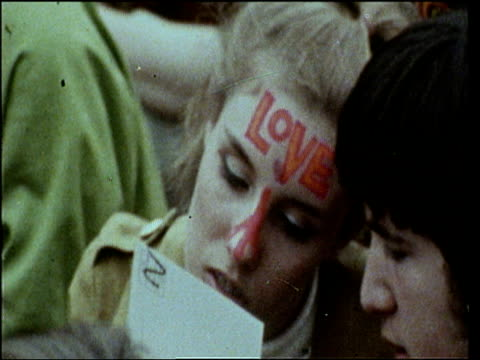 Girl with 'love' written on her forehead looks at piece of card at Love in festival 1967