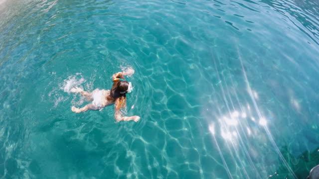 Fille avec un masque de plongée avec masque et tuba dans les eaux bleu clair de l'eau de mer
