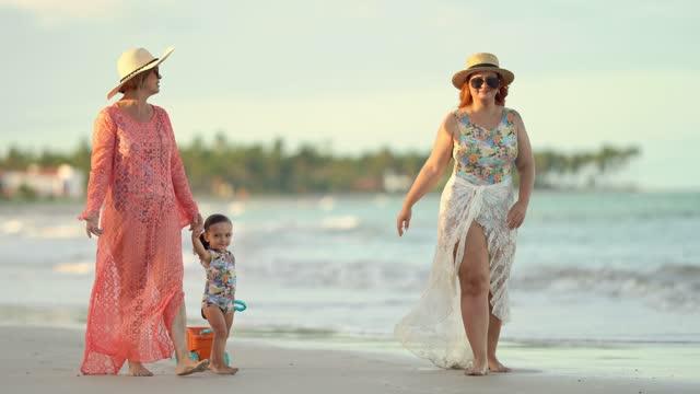vídeos y material grabado en eventos de stock de niña con madre y abuela caminando por la playa - pasear en coche sin destino