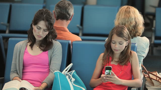 MS Girl (8-9) with mother waiting in airport lounge, girl talking on cell phone, Appleton, Wisconsin, USA