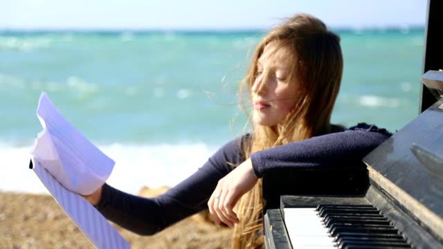 vidéos et rushes de fille avec des notes sur la côte - partition musicale
