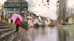 Girl with pink umbrella walks forward on Strasbourg Canal Staircase
