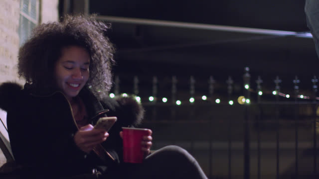 vídeos de stock e filmes b-roll de ms. girl with plastic drink cup smiles as she texts on smartphone at party. - mensagem sms