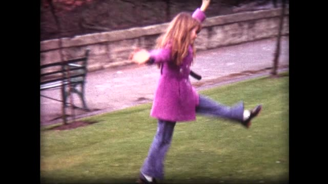 1968 girl with red hair, in pink coat does multiple cartwheels on green grass - nur kinder stock-videos und b-roll-filmmaterial