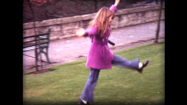 stockvideo's en b-roll-footage met 1968 girl with red hair, in pink coat does multiple cartwheels on green grass - alleen kinderen