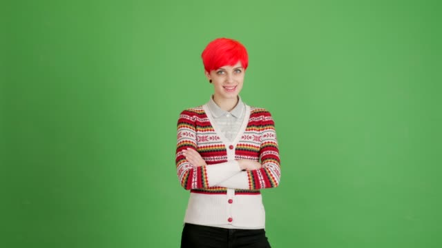 girl with red hair looks at the camera and smiles on a green background - blouse stock videos & royalty-free footage