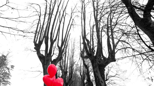 girl with red heart shaped balloons waiting in park - mgost stock videos and b-roll footage