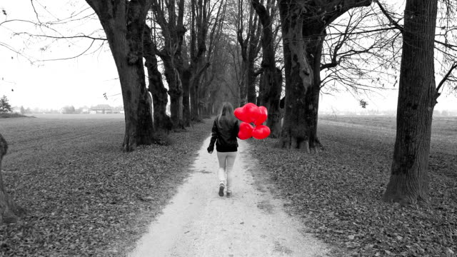 Girl with red heart shaped balloons walking in park
