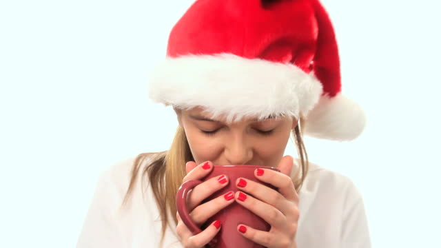 girl with santa hat drinks from a coffee mug. - santa hat stock videos & royalty-free footage