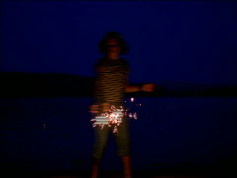Girl with sparkler dancing on lakeshore at dusk