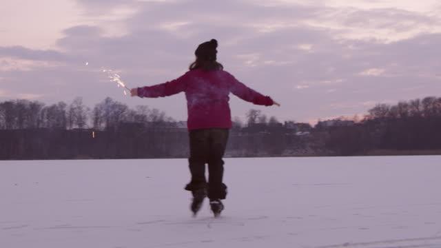 4K Girl with sparkler ice skating on frozen lake, slow motion