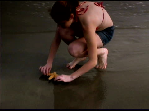 vídeos de stock, filmes e b-roll de girl with starfish on beach - only teenage girls