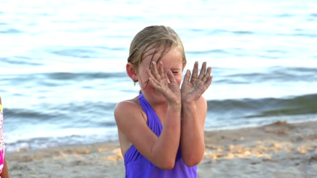Girl with water balloon popping in her face at beach