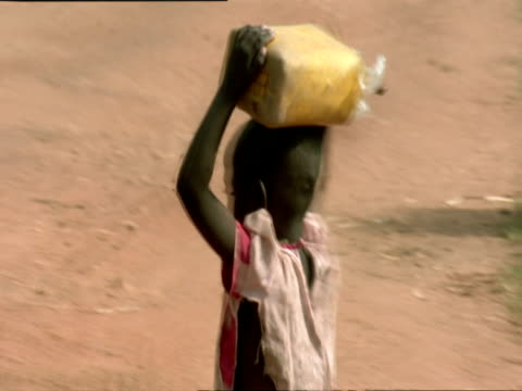 ms ts pan girl with water container on her head running away from camera / kigali, rwanda - 運ぶ点の映像素材/bロール