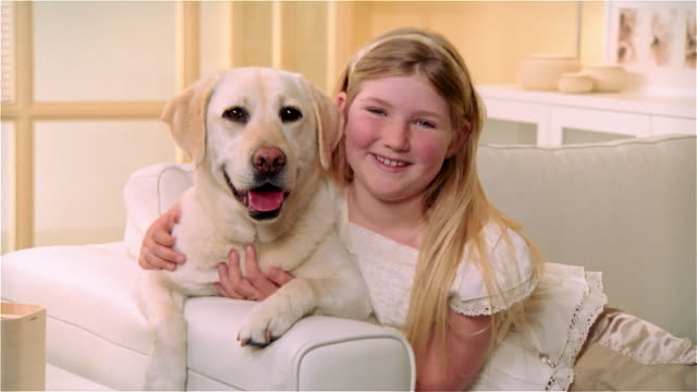 CU, Girl (8-9) with Yellow Labrador in living room, portrait