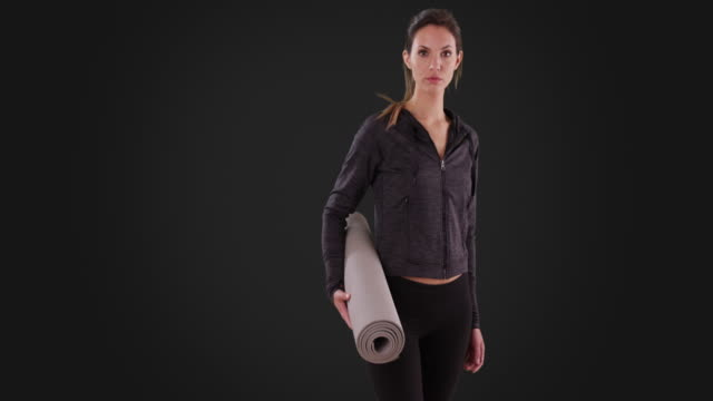 stockvideo's en b-roll-footage met girl with yoga mat walks to center screen and looks at camera on gray background - vaste stof