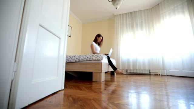 stockvideo's en b-roll-footage met meisje werken in slaapkamer - dubbel bed