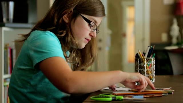stockvideo's en b-roll-footage met girl working on a school project. - omsloten ruimte