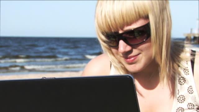 vídeos y material grabado en eventos de stock de chica trabajo en portátil en el mar de alta definición - sólo mujeres jóvenes