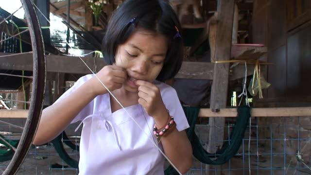vídeos y material grabado en eventos de stock de ms td girl working with hands spinning wheel / rangoon, myanmar - niñez